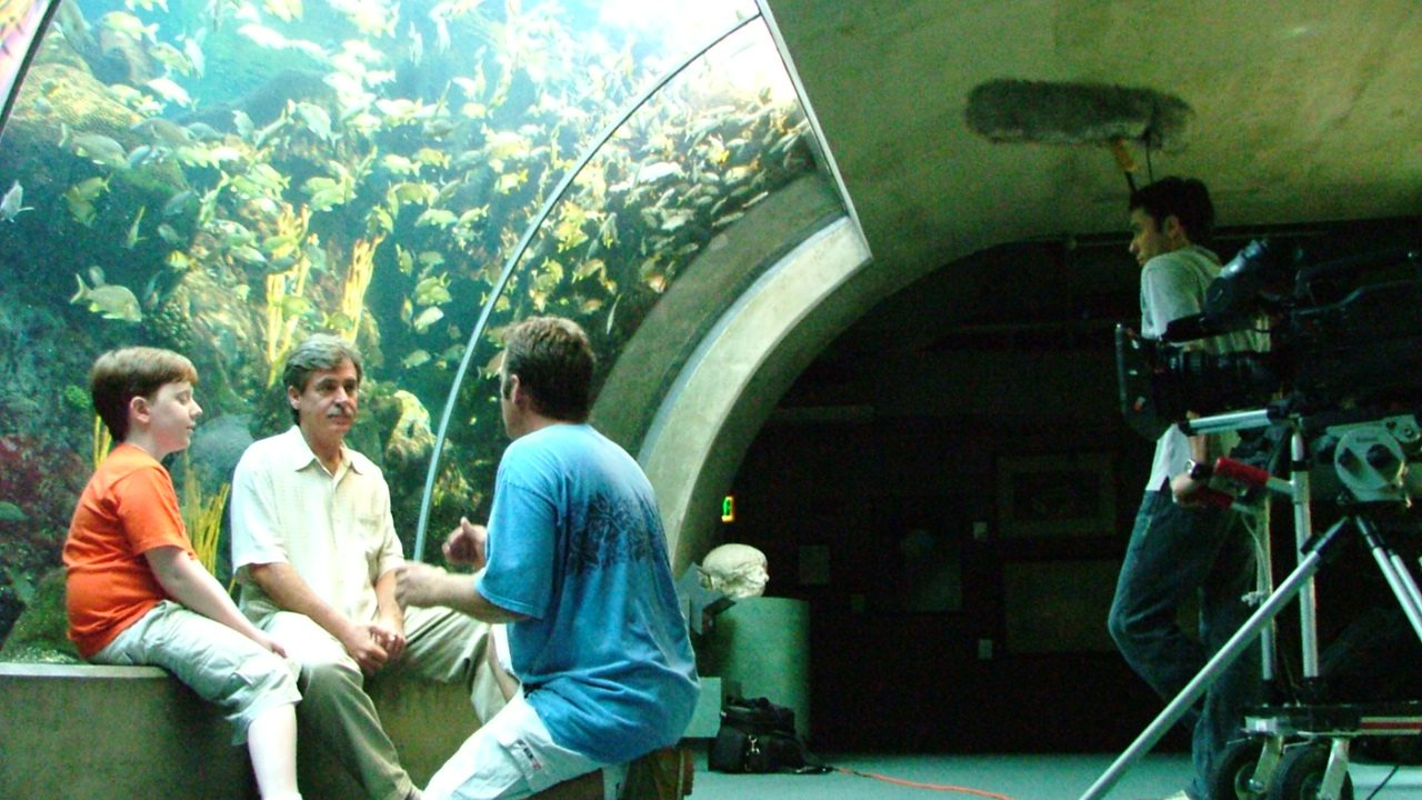 Child and older male sit in front of aquarium fish tank in aquarium tunnel with director providing instructions in front of RED Epic Camera with Boom Mic Operator Standing besides camera tripod