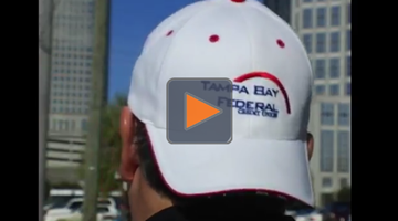 Guy wearing Tampa Bay Federal Credit Union hat backwards while riding a motorcycle