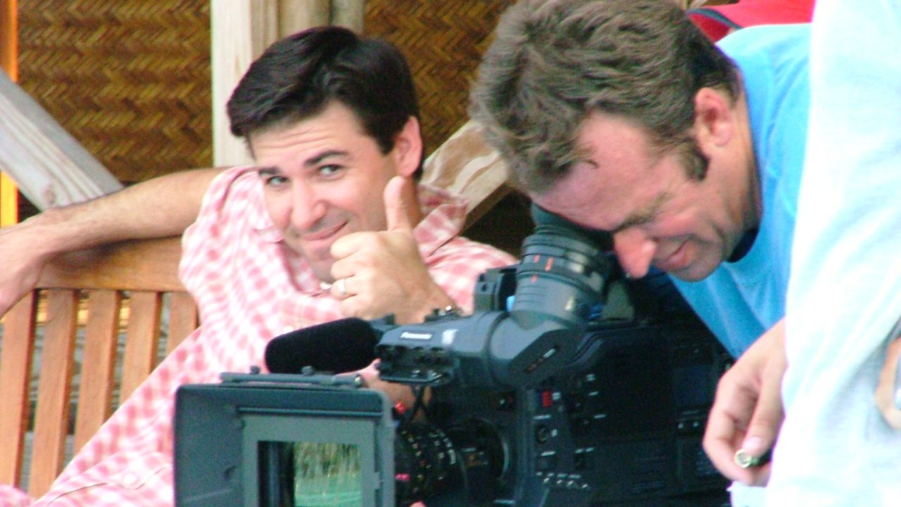 Handsome Man gives thumbs up to camera next to movie director looking into ARRI Alexa viewfinder